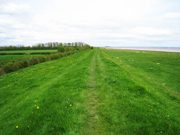 The Wales Coast path on top of the levee near Caldicot- view looking back to Severn Bridge photographed by Charles Hawes. Walking in Wales.