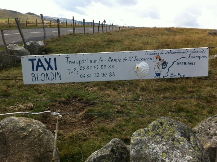 Advert for taxi service between Aumont Aubrac and Nasbinals on the Way of St James, photographed by Charles Hawes. Route St Jacques. GR65