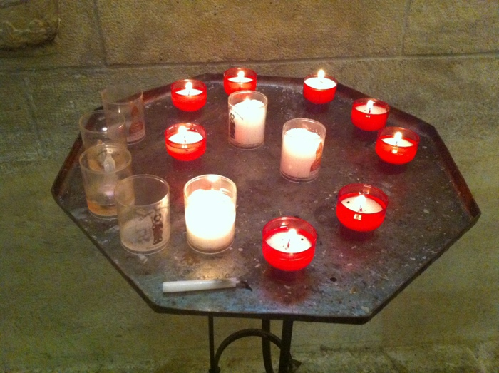 Candles in the church opposite the castle Walking The way of St James between St Come D'Olt and Estaing written and prohotographed by Charles Hawes. Route St Jacques.