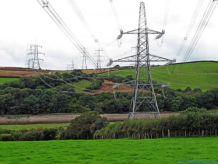 Electricity pylons across the River Towy from the Wales Coast Path between Kidwelly and Carmarthen, photographed by Charles Hawes. Walking in Wales.