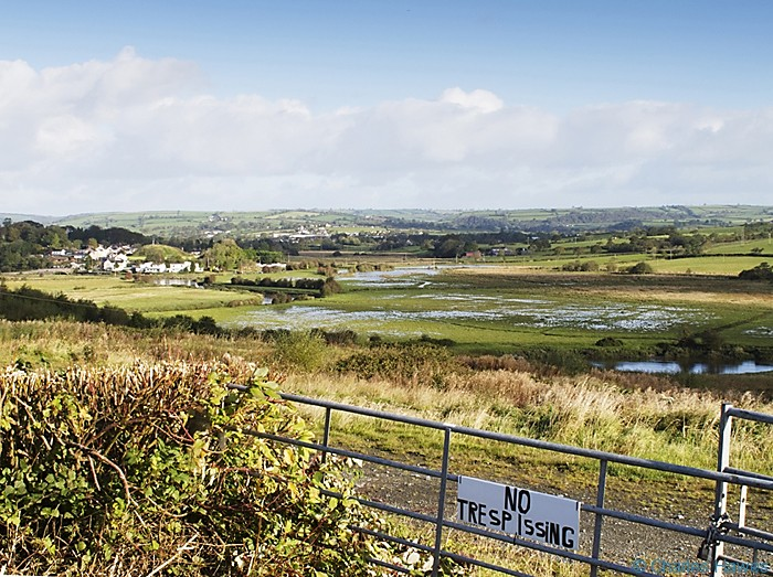 Flooded land on the outskirts of St Clears, photographed from the Wales Coast Path by Charles Hawes. Walking in Wales.