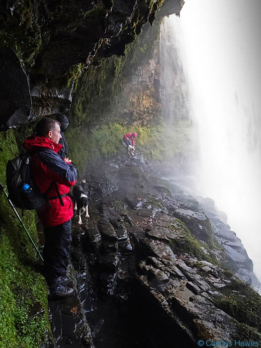 Inside the Sgwd yr Eira waterfall on the river Hepste in Powys, Wales photographed by Charles Hawes. Walking in wales..
