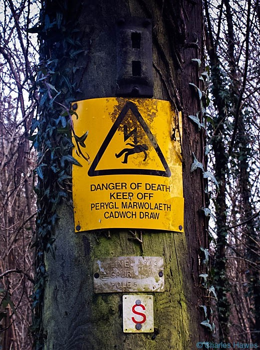 Warning sign on electricity pole, photographed by Charles Hawes