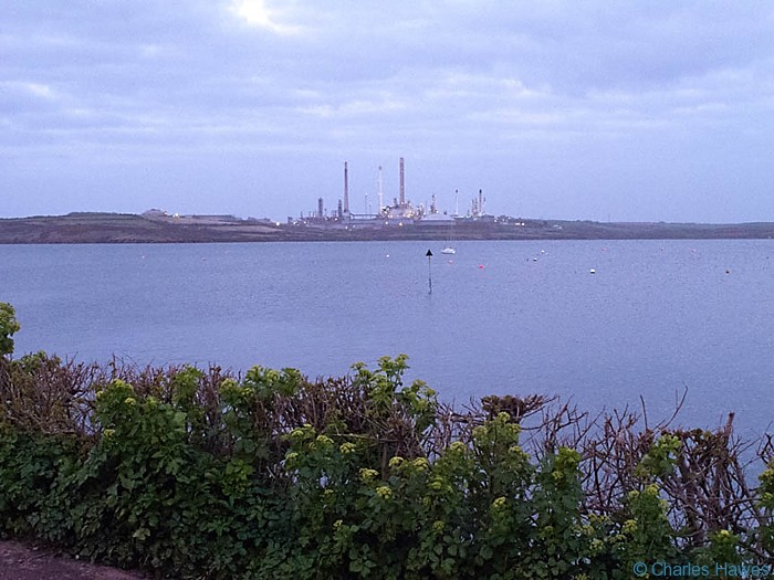 Oil refinery at dusk on Angle Bay, Pembrokeshire, photographed from the Wales Coast path by Charles Hawes