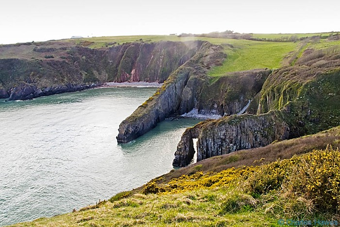 Natural arch and bay on the Wales Coast Path near Manorbier, Pembrokeshire. Image by Charles Hawes