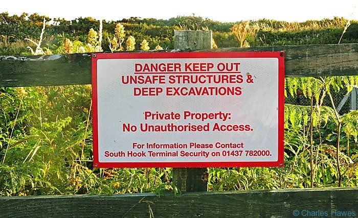 Warning sign on The Wales Coast Path near South Hook Point in Pembrokeshire, photographed by Charles Hawes
