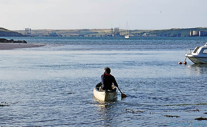 Canoe in Sandy Haven, Pembrokeshire with view across Milford Haven, photographed by Charles Hawes