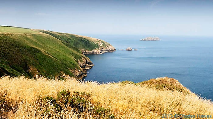 Sloping cliffs near Ticklas Point photographed from The Wales Coast Path by Charles Hawes