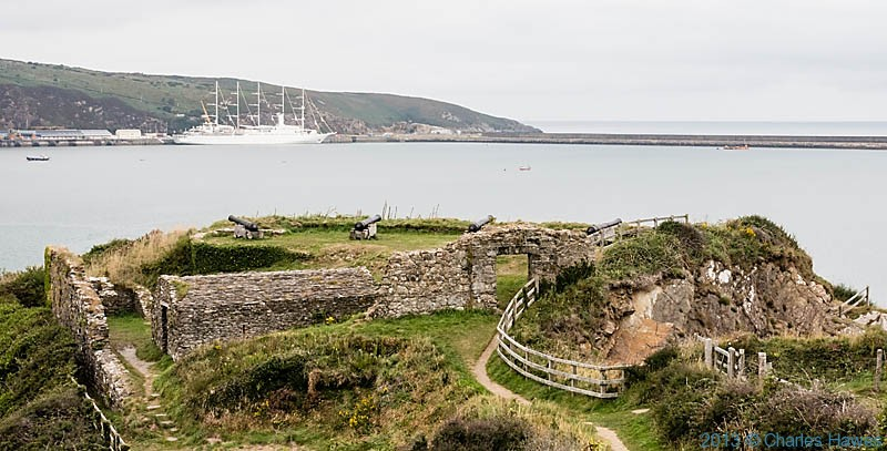 Sailing cruiser in Fishguard harbour with Castle Point in foreground, photographed from The Wales Coast Path by Charles Hawes