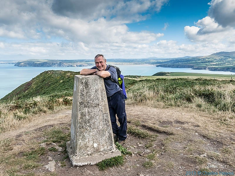 Charles Hawes at the trig point at Dinas Island, photographed from The Pembrokeshire Coast path by Neil Smurthwaite