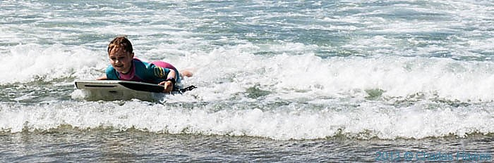 Girl surf-boarding at Whitesands Bay, Pembrokeshire, photographed from The Wales Coast Path by Charles Hawes